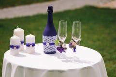 Casarse los vidrios y las botellas adornados del champán en la tabla Imagenes de archivo