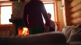 Casarse pares en el amor que calienta en suéteres rojos por la chimenea Novia y novio relajarse y besarse por el fuego caliente y