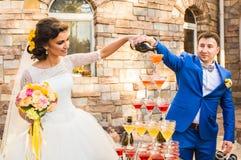 Casarse pares está vertiendo el champán al aire libre Vidrios coloridos para el alcohol con las bayas Fotografía de archivo
