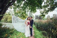 Casarse pares románticos en parque en día de boda Novio Hugging Bride foto de archivo libre de regalías