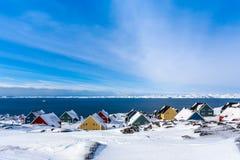 Casas amarelas, azuis, vermelhas e verdes do inuit cobertas na neve no Foto de Stock