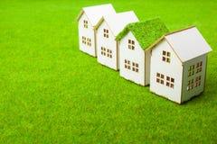 Casas arranjadas na fileira no campo gramíneo Foto de Stock