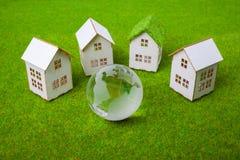 Casas arranjadas na fileira no campo gramíneo Imagem de Stock