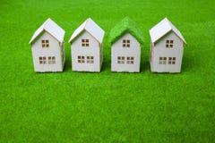 Casas arranjadas na fileira no campo gramíneo Fotografia de Stock Royalty Free