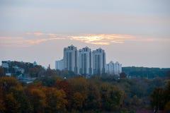 Casas bajo puesta del sol, nubes anaranjadas sobre edificios de varios pisos imagen de archivo