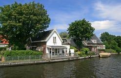 Casas, barco, canal e árvores holandeses fotografia de stock