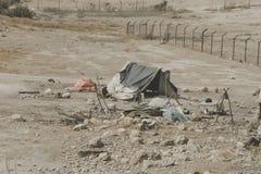 Casas beduínas no deserto perto do Mar Morto Regiões pobres do mundo Um beduíno indigente que senta-se na barraca Pobreza em Jord fotografia de stock