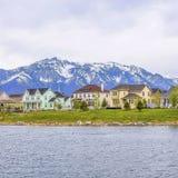 Casas bonitas do quadrado do quadro na frente de um lago calmo cintilando com a costa gramínea luxúria imagem de stock royalty free