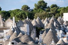Casas cónico-cubiertas blanqueadas tradicionales en el área de Rione Monti de la ciudad de Alberobello en Puglia, Italia del sur foto de archivo