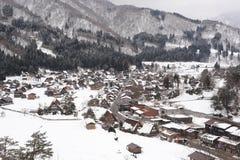 Casas cobridas com sapê do telhado cobertas na neve no inverno Fotos de Stock Royalty Free