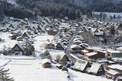 Casas cobridas com sapê do telhado cobertas na neve no inverno Foto de Stock