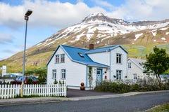 Casas coloridas en la pequeña ciudad Seydisfjordur en Islandia del este en verano con el lago y la nieve imagenes de archivo
