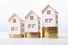 Casas com as pilhas de moedas Imagens de Stock
