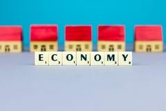 Casas da estatueta com sinal da economia Fotografia de Stock Royalty Free