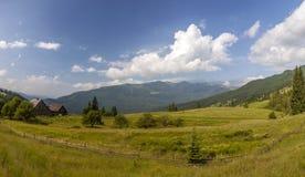 Casas da vila em montes com os prados verdes no dia de verão Imagem de Stock Royalty Free