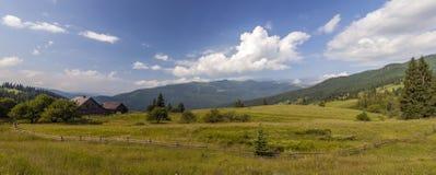 Casas da vila em montes com os prados verdes no dia de verão Fotos de Stock Royalty Free