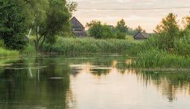 Casas da vila no banco de rio Fotos de Stock