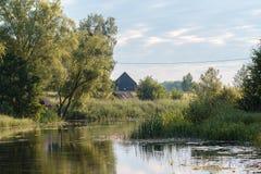 Casas da vila no banco de rio Imagens de Stock Royalty Free