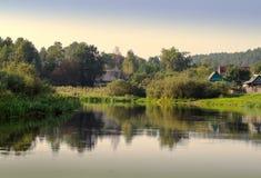 Casas da vila no banco de rio Imagem de Stock