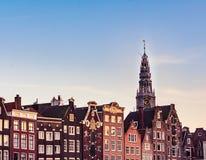Casas de Amsterdão com a torre colorida das fachadas e de igreja de Westerkerk durante o por do sol no canal do rio de Amstel em  foto de stock royalty free