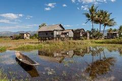 Casas de bambú simples y barco viejo en el lago Inle adentro foto de archivo