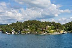 Casas de bloque a lo largo de la costa del Bjornafjorden Foto de archivo libre de regalías