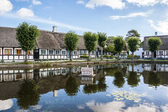 Casas de campo cobridas com sapê pela lagoa da vila Imagens de Stock Royalty Free