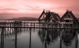 Casas de campo cobridas com sapê suspendidas em pernas de pau sobre o lago foto de stock
