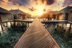 Casas de campo de madeira do molhe e da água Resort da ilha de Maldivas no por do sol fotografia de stock royalty free
