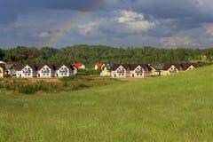 Casas de campo en el prado cerca del bosque Fotografía de archivo libre de regalías