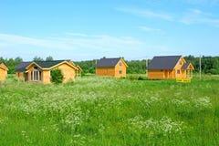 Casas de campo de madeira no campo verde para a venda foto de stock