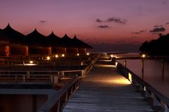 Casas de campo Maldivas da água do por do sol fotos de stock royalty free