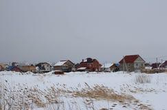 Casas de campo sob o setor privado da paisagem do inverno da construção no inverno em um lote vago na distância imagens de stock royalty free