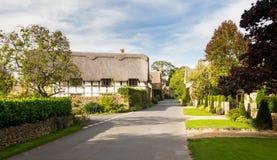 Casas de campo Thatched na rua principal de Stanton foto de stock