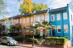 Casas de fileira coloridas com Windows branco e Front Doors de madeira fotografia de stock royalty free