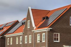 Casas de fileira modernas com as telhas de telhado vermelhas e os painéis solares fotos de stock