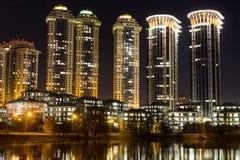 Casas de gran altura de un complejo residencial con la iluminación de la noche Vivienda costosa imagen de archivo libre de regalías