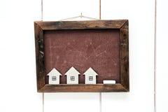 Casas de la cartulina en un fondo de un consejo escolar Fotografía de archivo