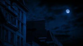 Casas de la ciudad en la noche debajo de la Luna Llena almacen de video