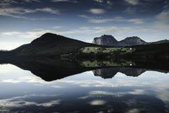 Casas de la granja que reflejan en un lago Fotografía de archivo