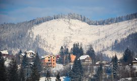 Casas de la montaña del centro turístico de la naturaleza de la nieve en las montañas en invierno fotos de archivo