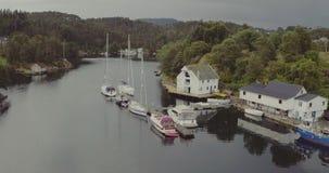 Casas de la visión aérea en costa del fiordo con los barcos de los yates en los embarcaderos metrajes