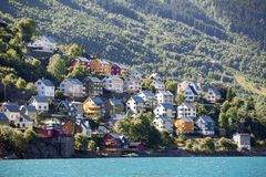 Casas de madeira coloridas para viver na inclinação de montanhas perto do fiorde norueguês, a cidade de Odda, condado de Hordalan fotos de stock
