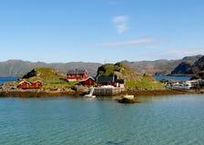 Casas de madeira do estilo norueguês colorido de uma aldeia piscatória pequena, cabo norte, Noruega Imagem de Stock