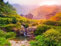 Casas de madeira e cachoeira pequena em terraços do arroz da espinha dorsal do dragão, Longsheng, Guangxi, China foto de stock royalty free
