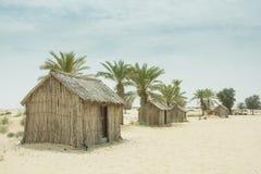 Casas de madeira pequenas árabes da vila do estilo antigo no deserto entre palmeiras Imagens de Stock Royalty Free