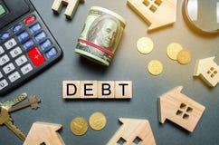 Casas de madeira, uma calculadora, chaves, moedas e blocos com o débito da palavra O conceito do débito para abrigar Hipoteca Rea imagens de stock