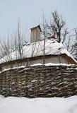 Casas de madeira velhas sob um telhado cobrido com sap? coberto com o suporte da neve e do woodpile perto das ?rvores velhas imagem de stock