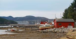 Casas de madeira vermelhas norueguesas e barcos de pesca pequenos na costa Fotografia de Stock Royalty Free