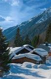 Casas de madera alpestres cubiertas con nieve. Fotos de archivo